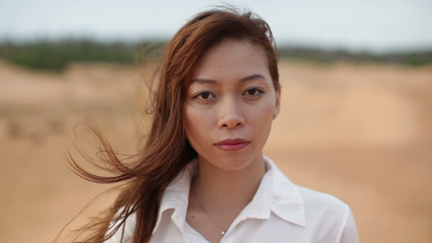 Asian woman serious sad looking outdoor desert wind blowing hair, close up face of young girl