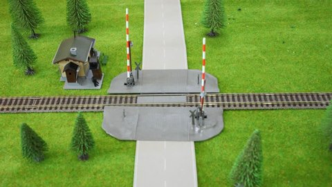 Model railway crossing: the car is moving and moving train it knocks. Stop motion.