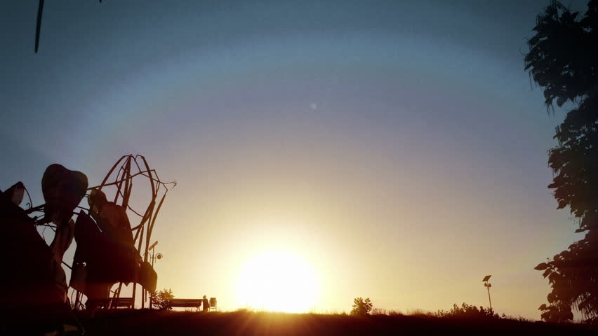 People silhouettes in parc with sun shining behind   Shutterstock HD Video #12789419