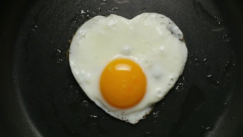Egg in frying pan. Form of heart. Cooking fried egg in the form of heart. ?lose-up 4K UHD 2160p footage.