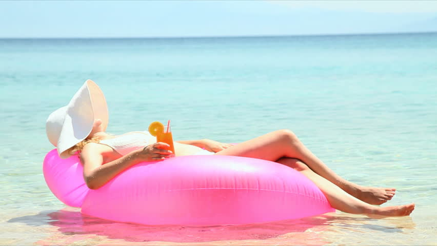 female on lilo with cocktail in her hands