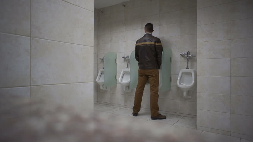 Man walks into a public washroom and uses the urinal.