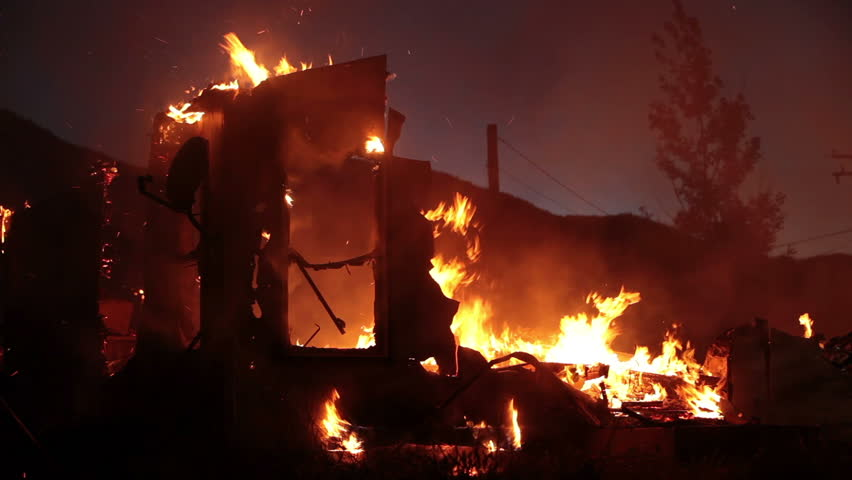 Fireman working and walking as a silhouette on a house fire after dark at night, pushing burning wall down. Flames consume entire home.