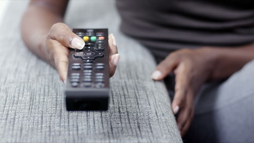 Young woman on sofa at home, changing tv channel with remote control | Shutterstock HD Video #1287754