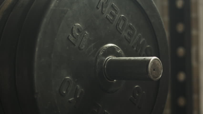 Transition shot of determined muscular man putting heavy plates on barbell and lifting in gym