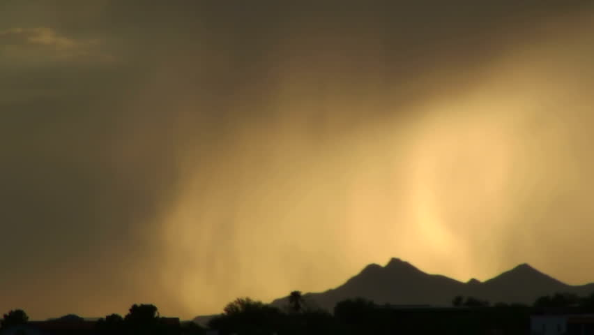 Time Lapse, Dramatic monsoon storm dumps swirling ribbons of rain on mountain landscape.