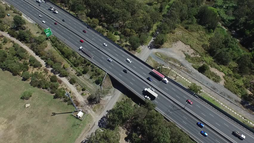Aerial view semi trailer lorry trucks, vehicles and cars with freight transport traveling on city high speed freeway or motorway driving scenes on open road. Gateway Motorway, Queensland Australia.