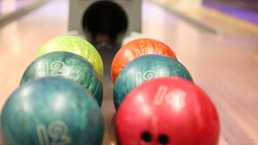 Close-up of varicolored bowling balls, man takes ball
