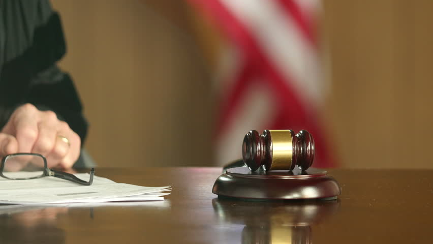 Gavel pounding on courtroom desk, close up