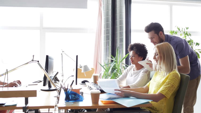 Business, startup and people concept - happy creative team with computers and folder discussing project in office | Shutterstock HD Video #12964544