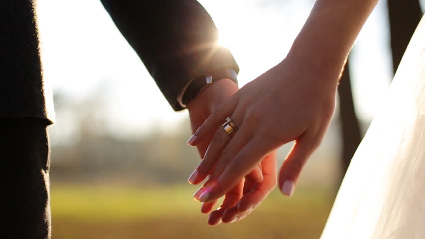 Wedding couple holding hands on sunset background shot in slow motion