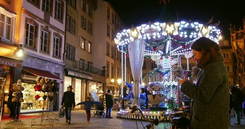 STRASBOURG, FRANCE - CIRCA 2015: Woman using Mobile Phone at Christmas Market with visitors admiring traditional carousel Christkindlesmarkt Christmas Market in Strasbourg, Place de la Cathedrale