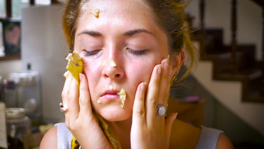 An attractive, young woman, wipes and blows bananas off her face as she looks irritated, pissed and annoyed while looking at the camera.