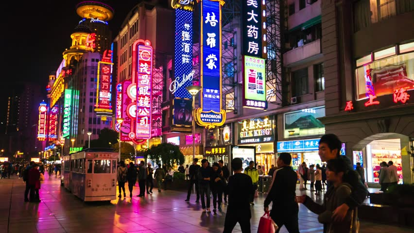 Shanghai - November 2015: Hyperlapse of Nanjing Road with people and colorful signboards glowing at night. 4K resolution