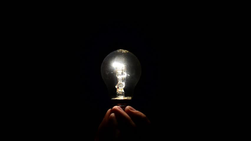 lighting for dark rooms. hand holding a light bulb in the dark lamp lights up hd stock lighting for rooms