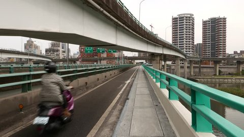 TAIPEI, TAIWAN - FEBRUARY 12, 2015: POV walk along pedestrian way on Zhongxiao Bridge, exit lane viaduct overhead, pass under. Dedicated motorbike section, separated from car traffic roadway