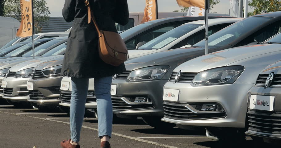STRASBOURG, FRANCE - CIRCA 2015: Woman walking between rows of Volkswagen cars and choosing the right Volkswagen after the Volkswagen Gate - Volkswagen emission scandal | Shutterstock HD Video #13088366