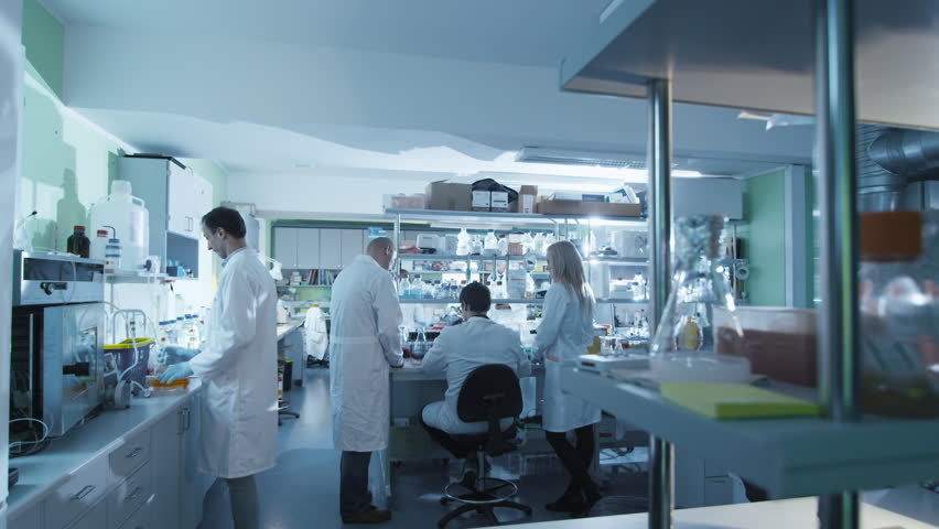 Timelapse footage of a team of scientists in white coats that are working in a modern laboratory. Shot on RED Cinema Camera in 4K (UHD).