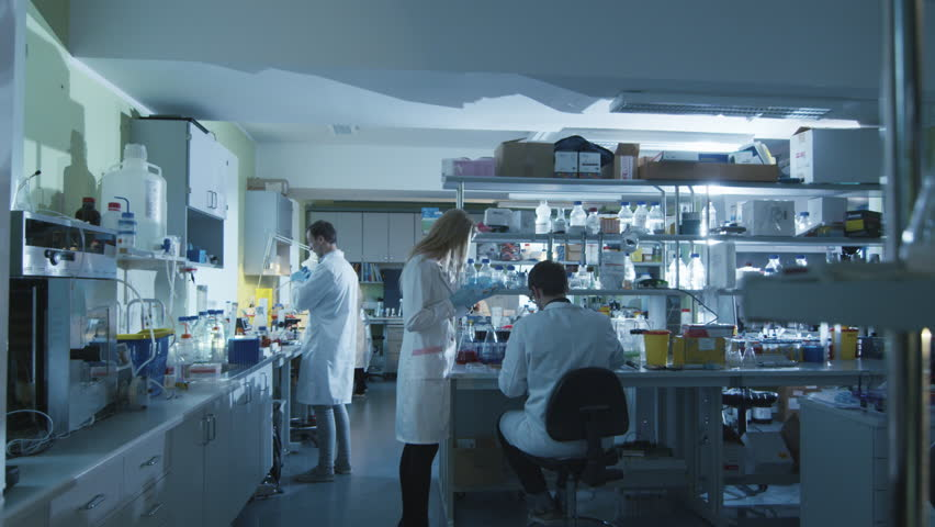 Team of caucasian scientists in white coats are working in a modern laboratory. Shot on RED Cinema Camera in 4K (UHD). #13089524