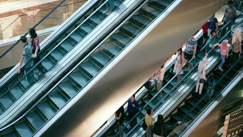SINGAPORE - CIRCA AUG 2015: People move on escalator staircases inside of shopping mall The Shoppes at Marina Bay Sands. Video UltraHD