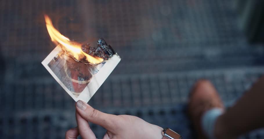 Beautiful sad woman burning photograph of her ex-boyfriend lover over bad relationship break up