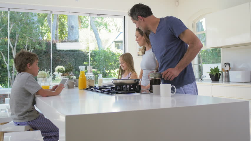 Young daughter walks into family kitchen in modern contemporary home while parents making healthy breakfast