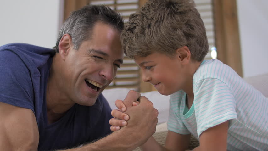 happy caucasian father and son kid competing in arm wrestling while both lying on the sofa couch at home having fun