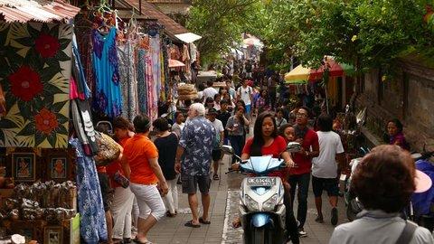 UBUD, INDONESIA - MARCH 14, 2015: Crowded market street in Ubud, overhead perspective shot, people walk along shopping area. Popular place, Jalan Karna, alley from Pasar Seni Ubud to Jalan Dewi Sita