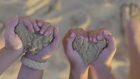 Teenage Girls Hold Sand In Their Hands (Create Heart Shapes) Then They Let Sand Blow Away