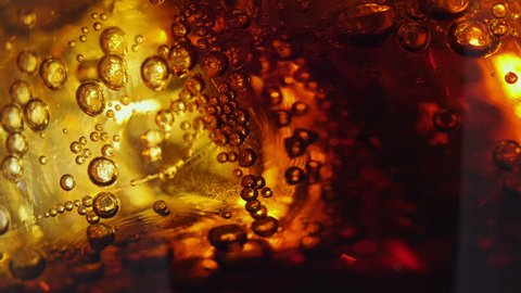 Cola and ice in glass. Cola pouring into a glass with ice cubes. close-up 4K UHD 2160p footage.