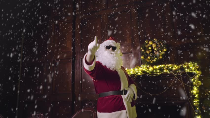 Santa Claus in sunglasses dancing and looking at the camera, tracking shot, snowfall, christmas tree with lights and decorated fireplace in background