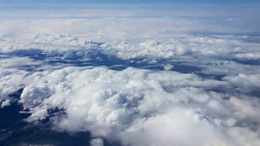 Traveling by air above clouds. View through an airplane window. Flying over the Mediterranean Sea through cirrus and cumulus clouds and little turbulence, showing Earth's atmosphere.