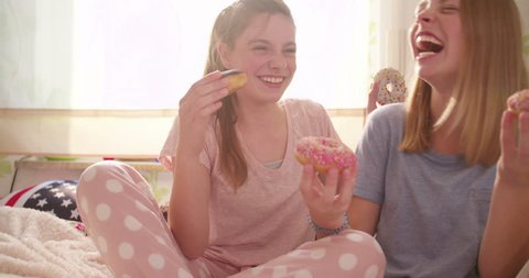 Laughing adolescent girl friends having fun in a sunlit bedroom eating colourful doughnuts while having a pyjama party