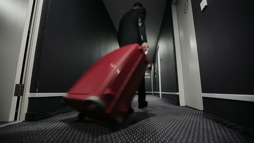 Businessman with a suitcase in a corridor of hotel. Slider camera movement