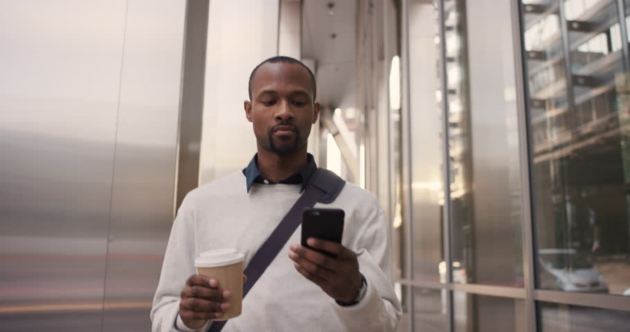 African American Man sms texting using app on smart phone in city. Handsome young businessman using smartphone smiling happy. Urban male professional commuting in his 20s | Shutterstock HD Video #13200104