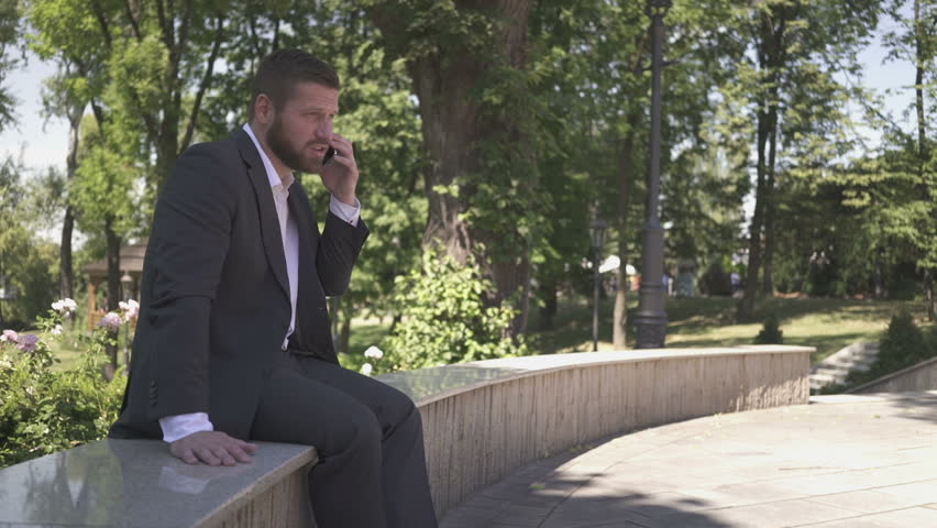 Businessman talking by smartfon, sitting on wall against park, pan shot.