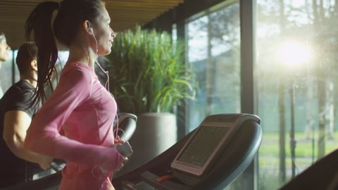 Attractive caucasian girl running on the treadmill in the sport gym with phone and earphones. Shot on RED Cinema Camera in 4K (UHD).