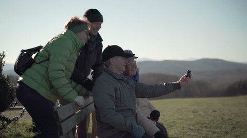 4k footage, four happy seniors taking selfies with handy on bench outside during their walk in hilly landscape