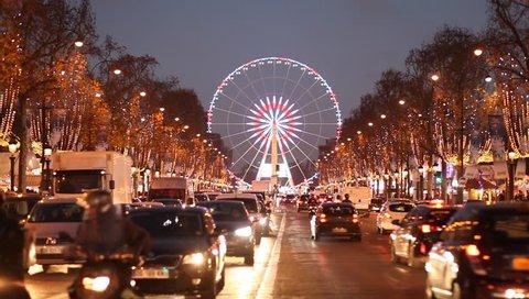 Illuminated ferris wheel in Concorde, night traffic at Champs-Elysees, Paris