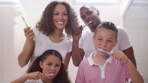 4K Happy mixed race family in bathroom cleaning their teeth together, as seen from the mirror's pov. Shot on RED Epic.