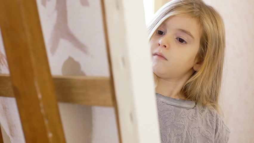 A pretty little girl painting with acrylic colors on a canvas, in a brightly lit room. Close-up shot.