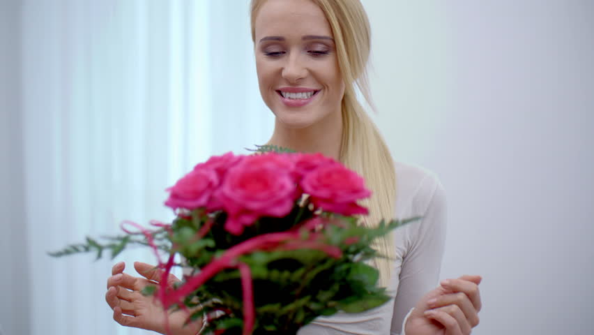 Happy young woman with a large bouquet of fresh pretty pink flowers exclaiming in surprise at the gift from her boyfriend on Valentines Day #13275884