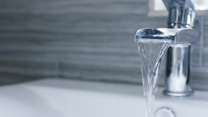 4K Running water from a waterfall tap in a bathroom, in slow motion