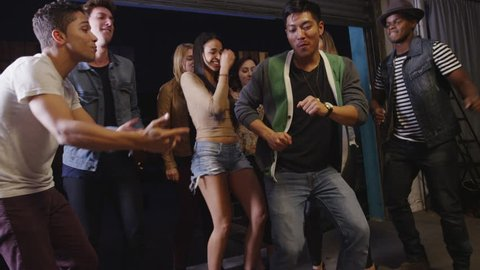 Happy fun loving hipster mixed race group of friends dancing late into night in cool open garage party