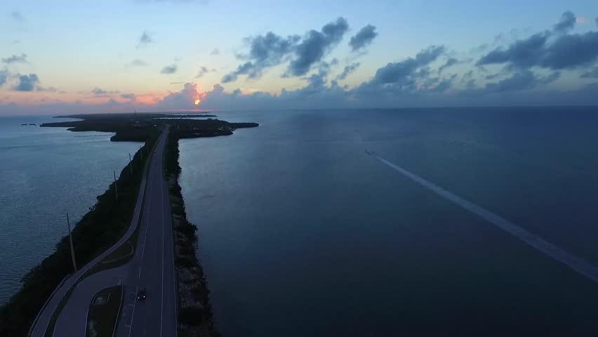 Aerial pan of ocean and jet ski on Overseas Highway in Florida Keys at sunset