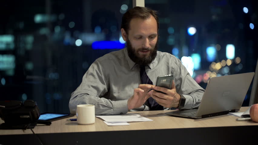 Young businessman using smartphone by desk in office at night    Shutterstock HD Video #13325564