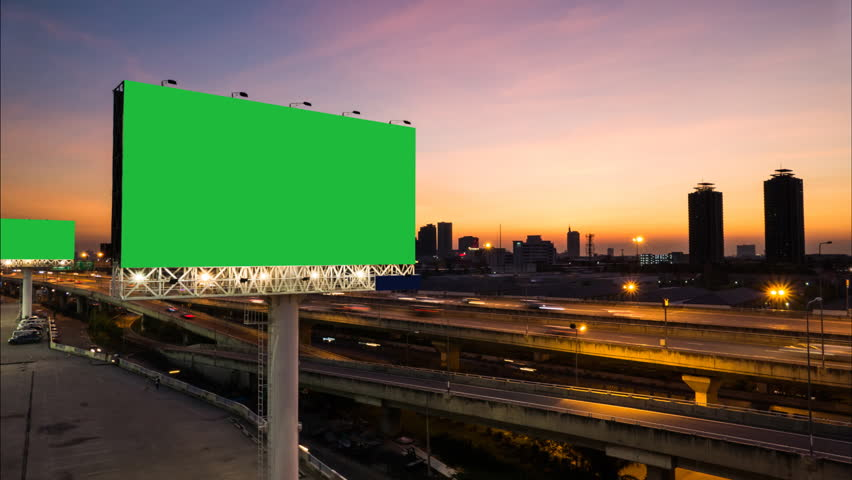 Advertising billboard green screen on sidelines of expressway with traffic at evening, time lapse.