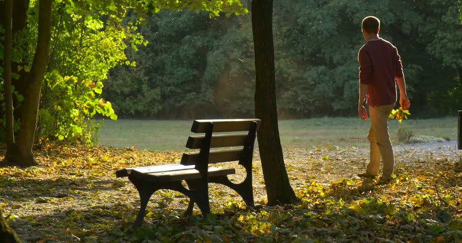 autumn scene athlete man seated   park bench