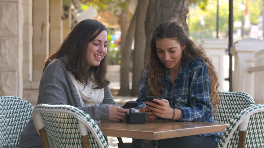 Two girls sitting in a cafe, drinking fruit smoothies and texting on their mobile phones | Shutterstock HD Video #13362044