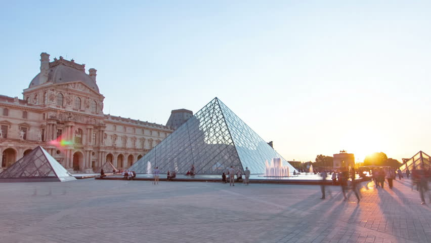 PARIS, FRANCE - APRIL 13, 2015:  Sunset shines through the glass pyramid of the Louvre museum timelapse hyperlapse